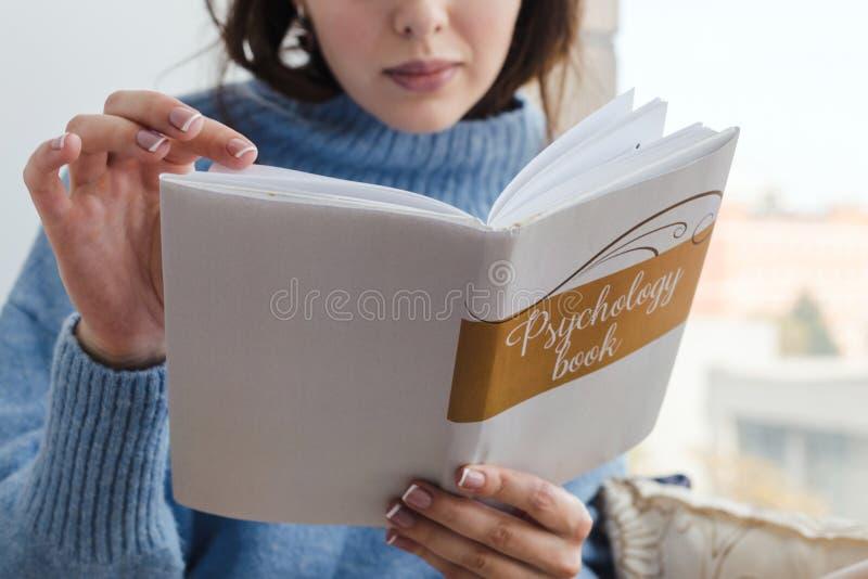 Närbild av en flicka i en blå tröja som läser en bok på psykologi nära fönstret royaltyfri fotografi