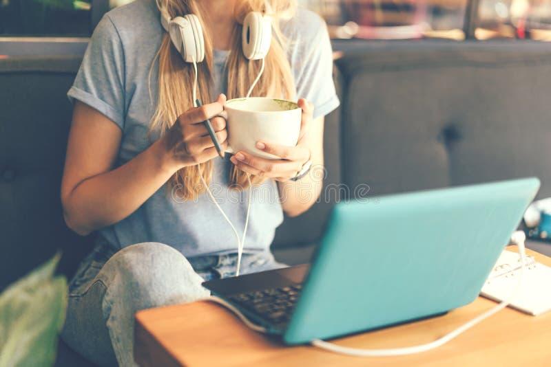 Närbild av en flicka med hörlurar och en bärbar dator arkivbilder