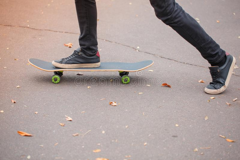 Närbild av en fot för skateboarder` s i svarta gymnastikskor arkivfoto