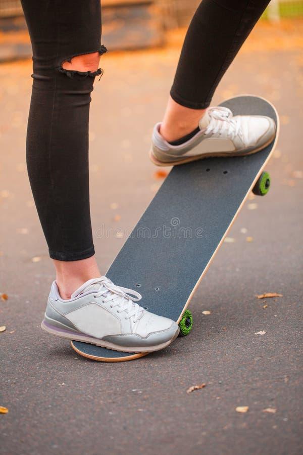 Närbild av en fot för skateboarder` s i svarta gymnastikskor royaltyfri bild