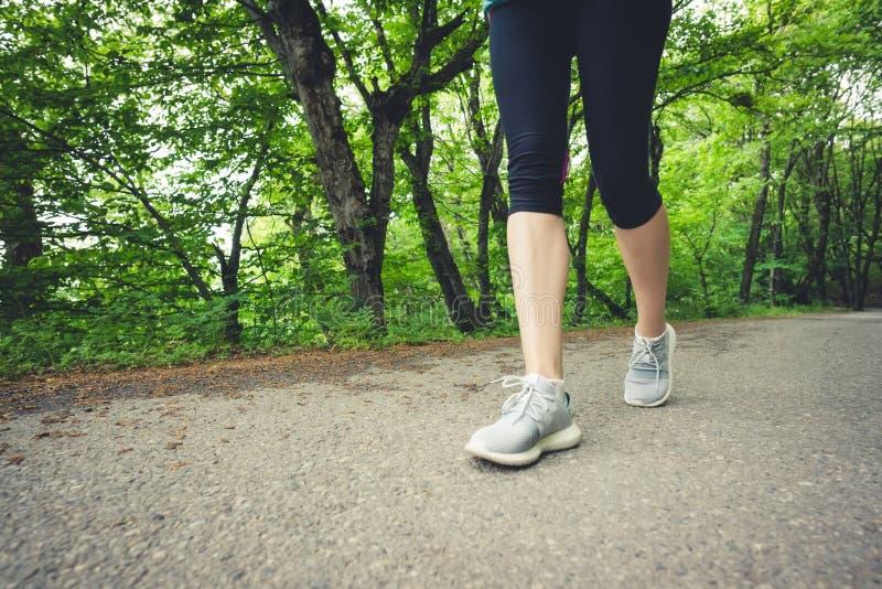 Närbild av en fot av en sportig flicka i damasker och gymnastikskor, innan att jogga i skogen begreppet av utomhus- sportar arkivbild