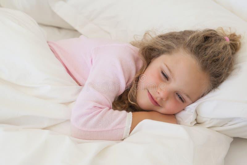 Närbild av en gullig flicka som sover i säng royaltyfri bild