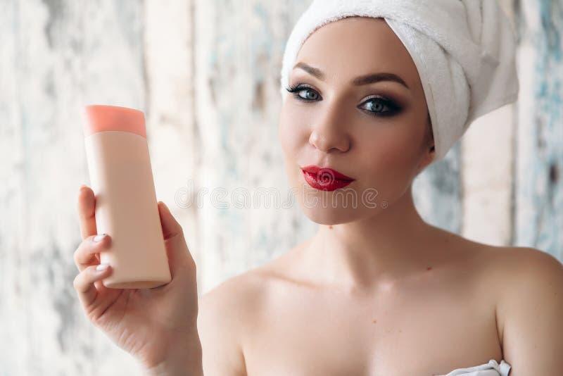 Närbild av en härlig ung flicka som precis har dykt upp från duschen som visar hennes smink, kvinna med en handduk på henne royaltyfria bilder