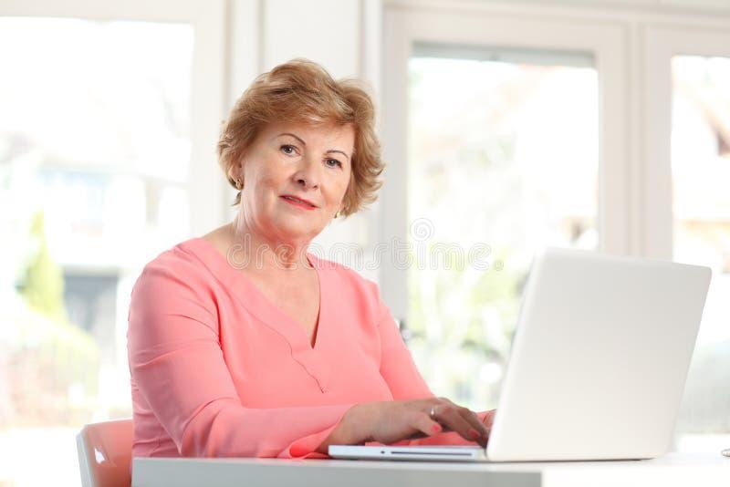 Närbild av en hög kvinna med bärbara datorn royaltyfri fotografi