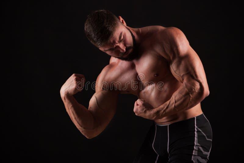 Närbild av en hand för ` s för maktkonditionman Den starka stiliga unga kroppsbyggaren visar hans muskler och biceps royaltyfri bild