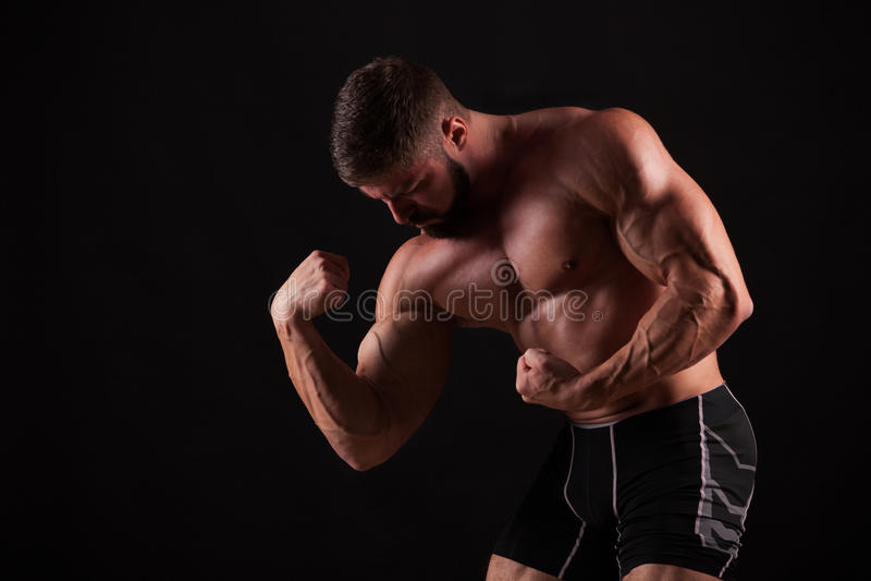Närbild av en hand för ` s för maktkonditionman Den starka stiliga unga kroppsbyggaren visar hans muskler och biceps arkivbild