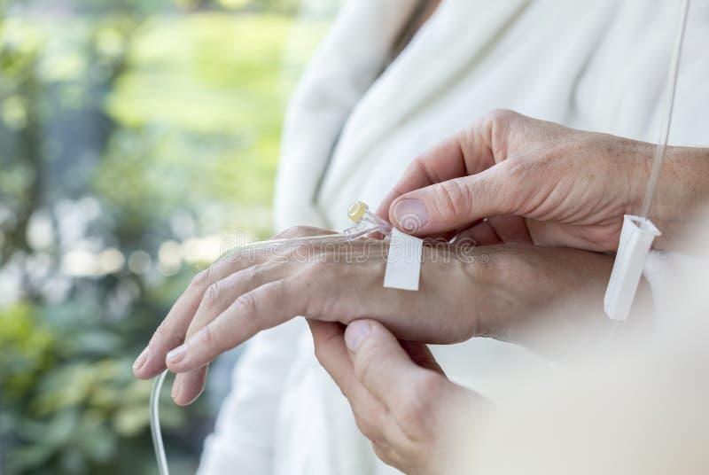 Närbild av en hand med en perifer venös tillträdeskateter royaltyfria foton