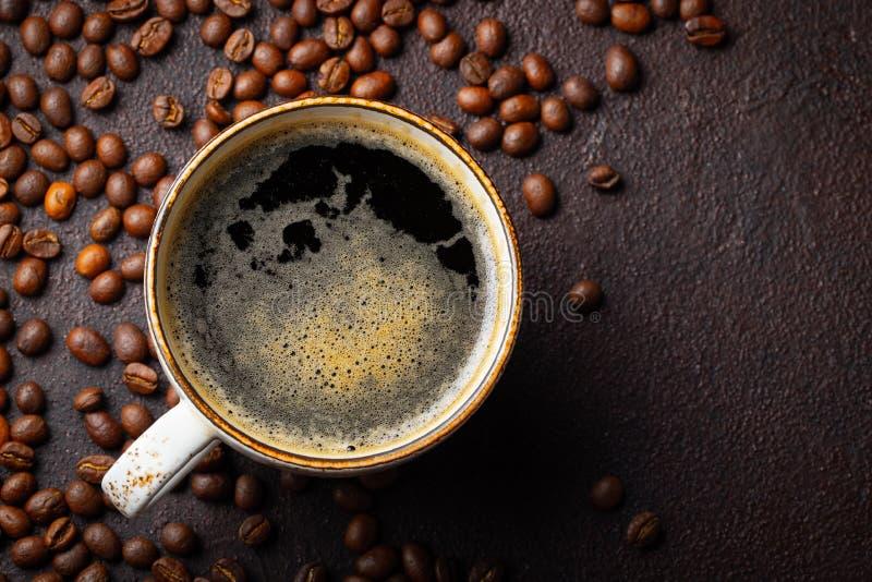 Närbild av en kopp av svart kaffe och kaffebönor på en mörk bakgrund Bästa sikt med kopieringsutrymme Lekmanna- lägenhet arkivfoto