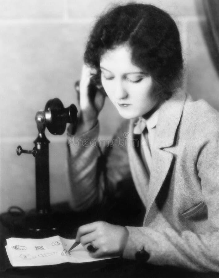 Närbild av en kvinna som talar på telefonen och drar på ett ark av papper (alla visade personer inte är längre uppehälle och inge royaltyfri foto