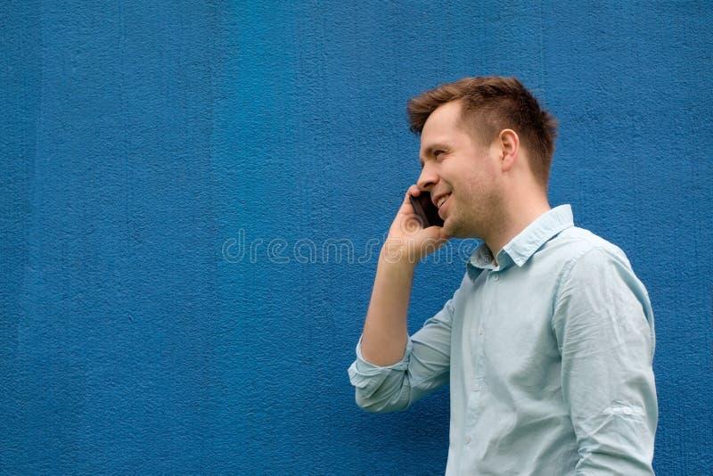 Närbild av en lyckad ung affärsman som talar på mobiltelefonen arkivfoton