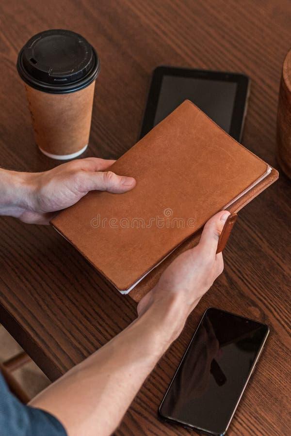 Närbild av en man som arbetar på ett skrivbord i ett kontor och rymmer anteckningsboken med copyspace arkivbild