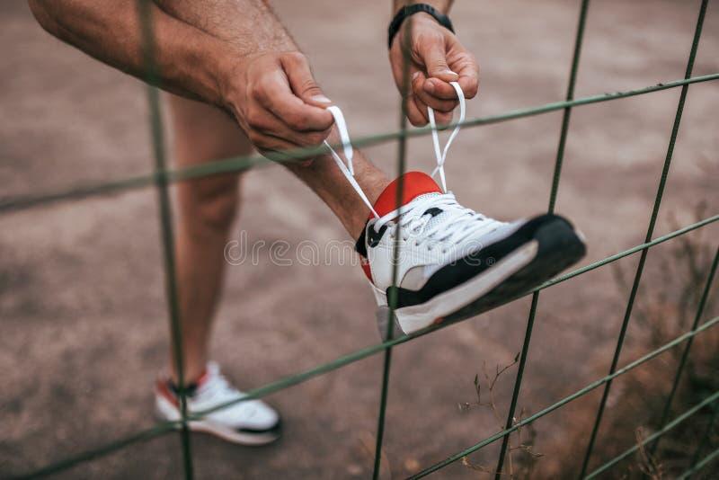 Närbild av en mans ben som binder skosnöre på en sko, i sommar i staden om ett staket eller staketet Sportlivsstil arkivbilder