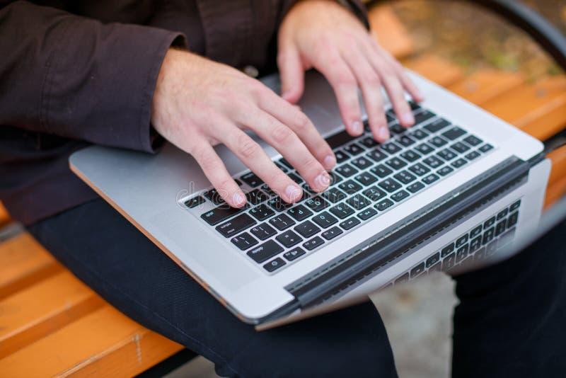 Närbild av en maskinskrivning för hand för man` s på en bärbar dator ovanför sikt arkivfoto