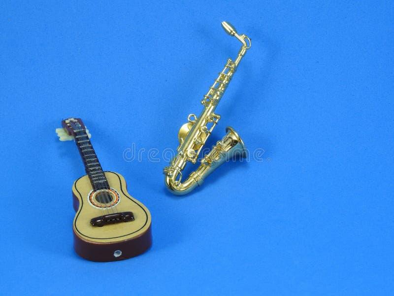Närbild av en miniatyrgitarr och saxofon på blå bakgrund fotografering för bildbyråer