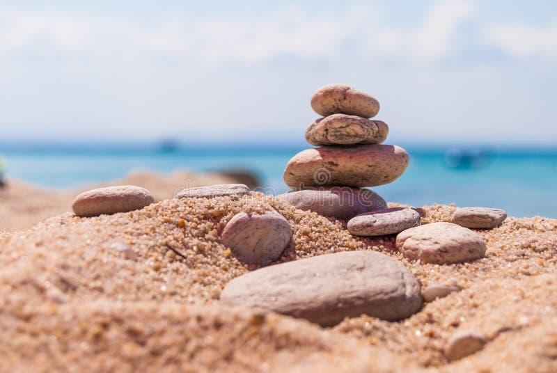 Närbild av en pyramid av stenar som läggas på en havsstrand royaltyfria bilder