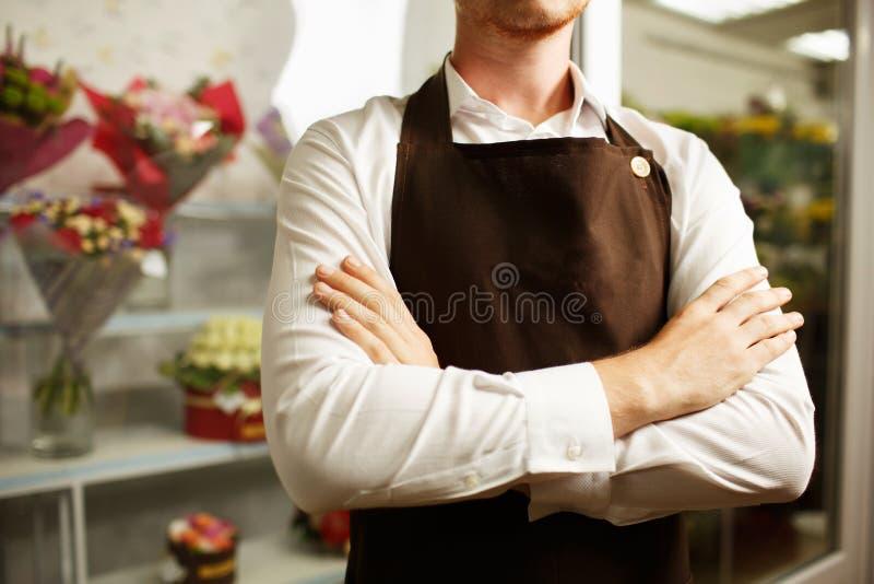 Närbild av en säker blomsterhandlare i ett brunt förkläde på en shoppabakgrund Blomsterhandlarelikformigbegrepp fotografering för bildbyråer