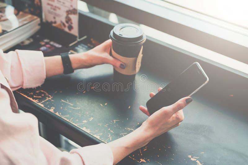 Närbild av en smartphone och en kopp kaffe i händerna av ett hipsterflickasammanträde i ett kafé på en svart tabell royaltyfria bilder