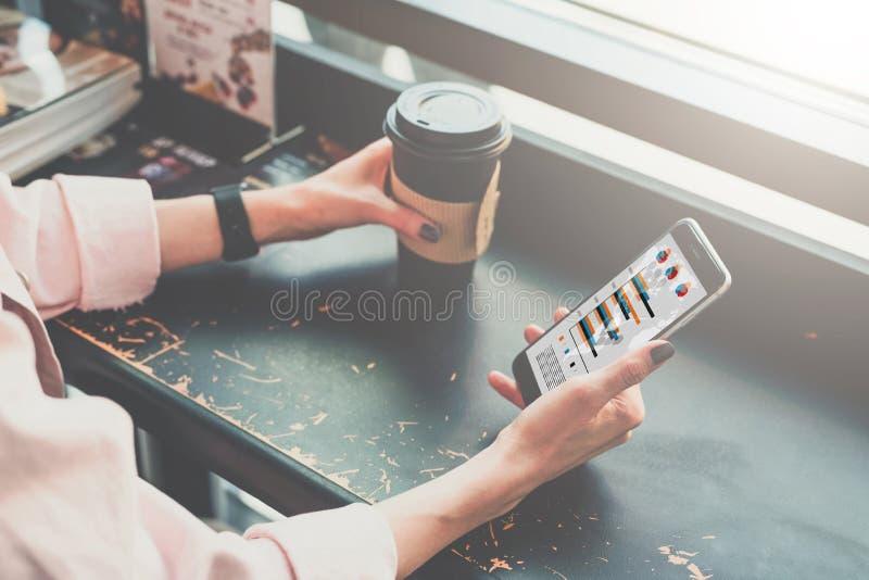 Närbild av en smartphone och en kopp kaffe i händerna av ett hipsterflickasammanträde i ett kafé på en svart tabell arkivbild