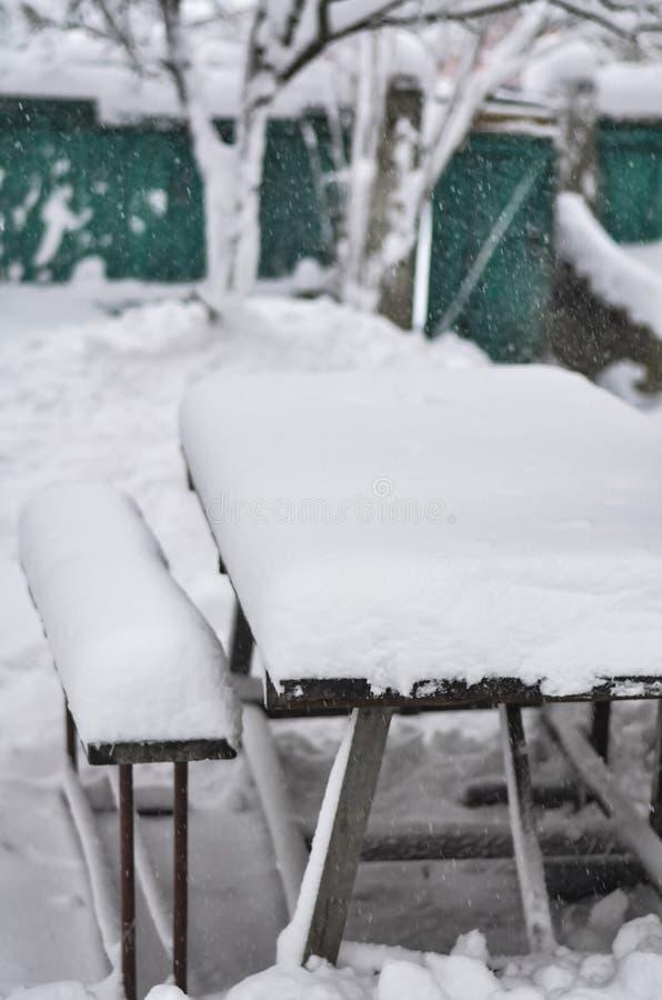 Närbild av en snöig gård med en tabell och bänkar under en snöstorm och en häftig snöstorm royaltyfria foton