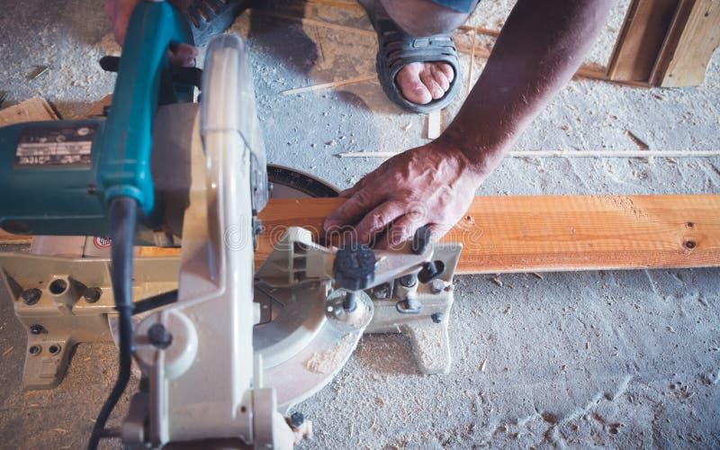 Närbild av en snickare som använder en cirkelsåg för att klippa ett stort bräde av trä royaltyfri fotografi
