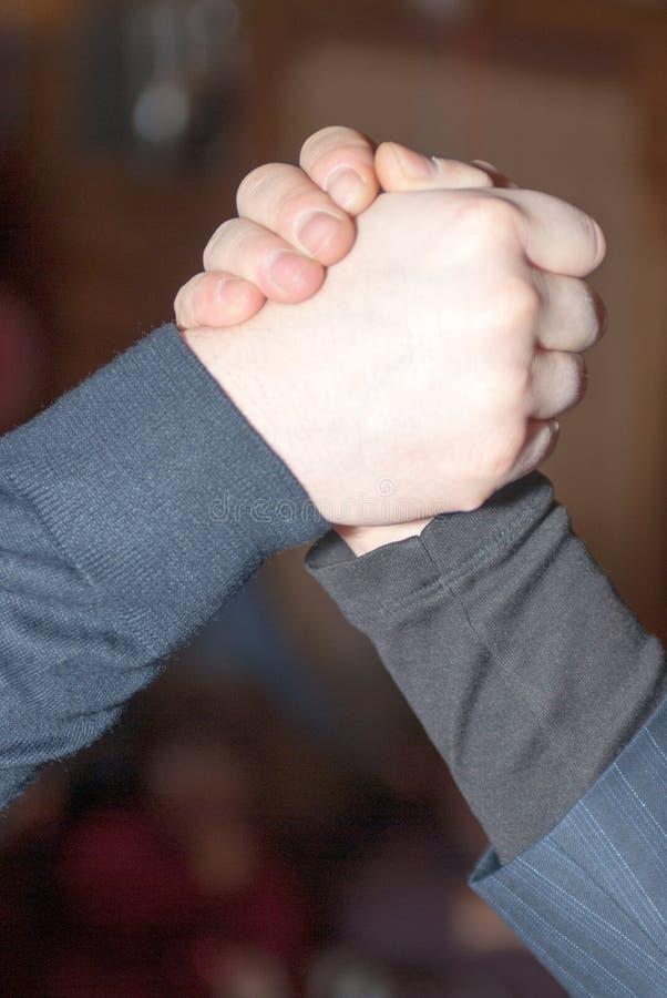 Närbild av en stark handskakning av två män i en halvpolokrage och en dräkt arkivfoton