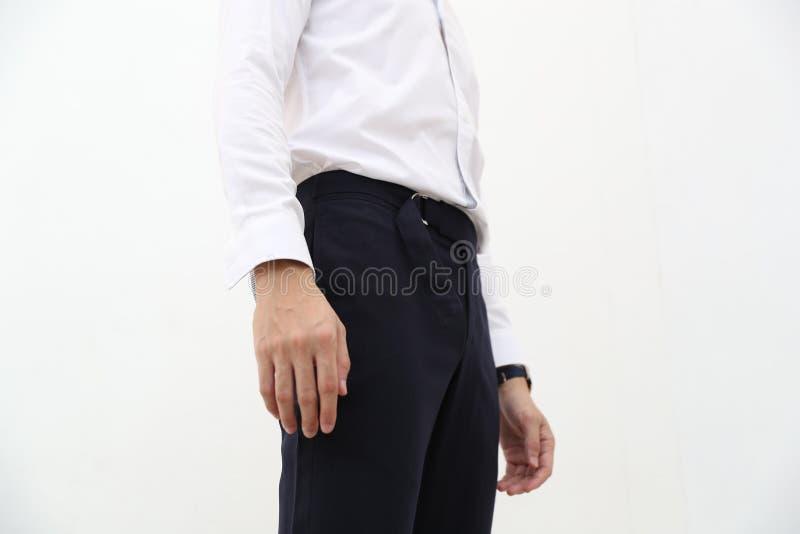 Närbild av en stilig man i den vita formella skjortan och svart lång byxa royaltyfri foto