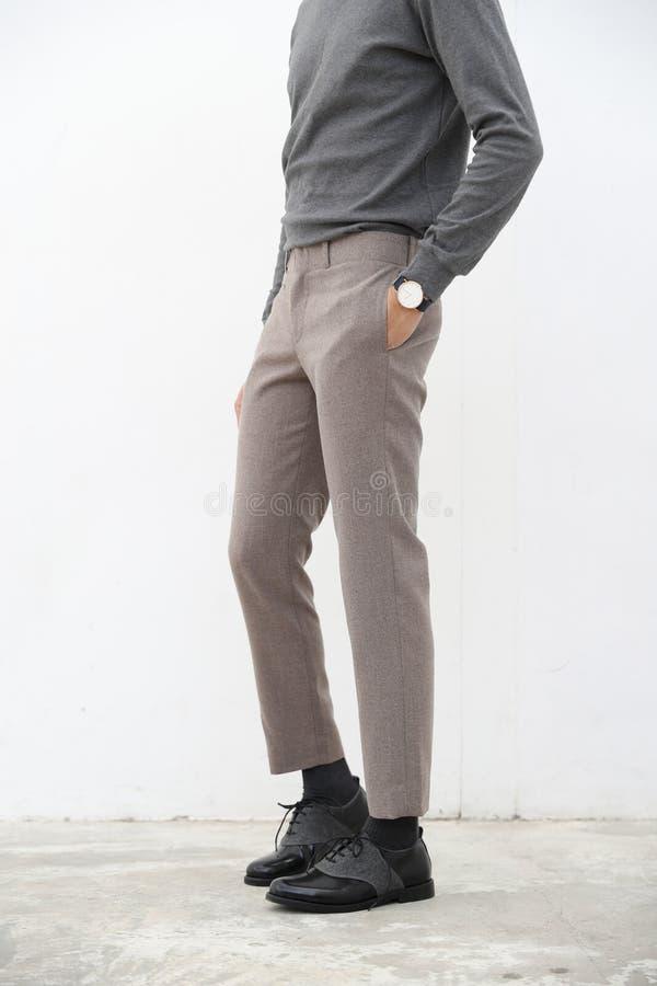 Närbild av en stilig man i grå halvpolokrageskjorta och lång byxa på vit bakgrund arkivfoton