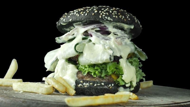 Närbild av en stor saftig hamburgare med en kotlett av gurkor som skivas med skivor och grönsallatsidor som hälls med all sås royaltyfria bilder