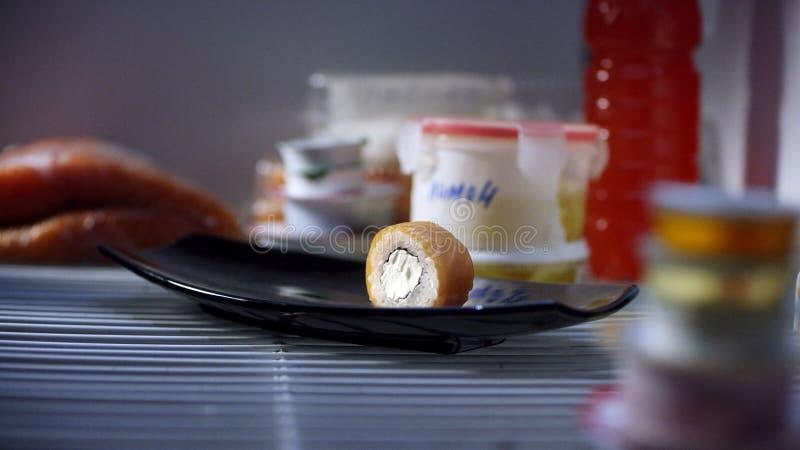 Närbild av en sushirulle på plattan Ensam sushirulle med laxen och ost är på den svarta plattan, som tar handen in arkivbild