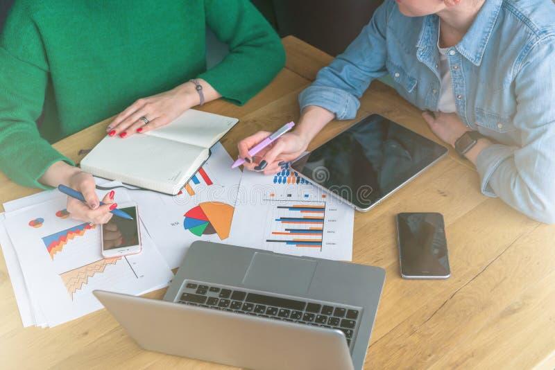 Närbild av en trätabell med pappers- diagram, bärbar dator, smartphones, minnestavladator royaltyfri foto