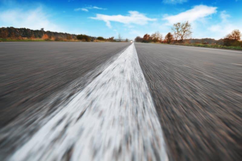 Närbild av en trafiklinje på en tom väg i rörelse med en skog och en himmel med moln på bakgrunden arkivfoton