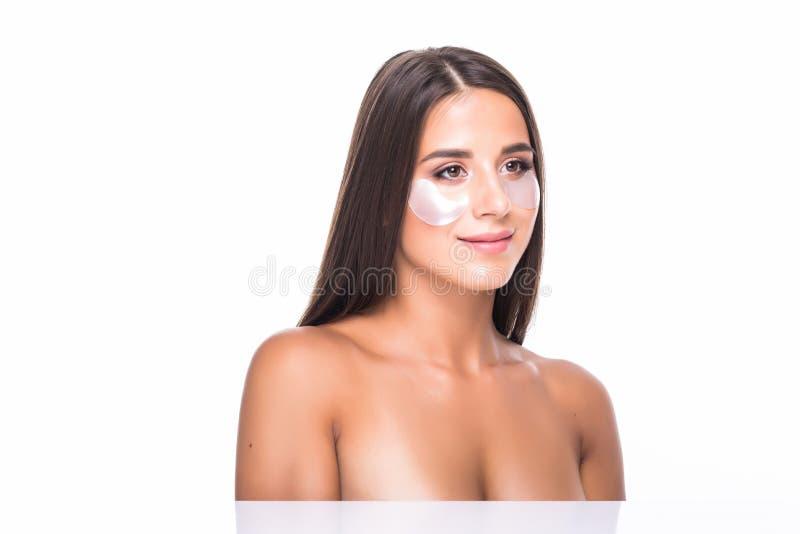 Närbild av en ung kvinna med lappar under ögon från skrynklor och mörka cirklar som isoleras på vit bakgrund arkivfoto