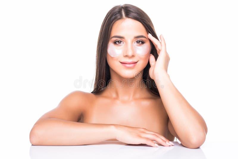 Närbild av en ung kvinna med lappar under ögon från skrynklor och mörka cirklar som isoleras på vit bakgrund arkivbild