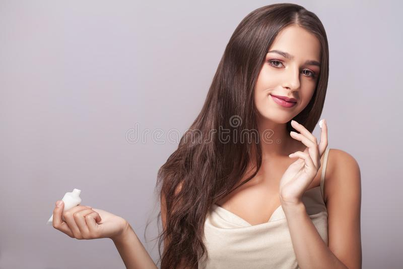 Närbild av en ung kvinna som får brunnsortbehandling isolerad white för cosmetic kräm arkivfoto