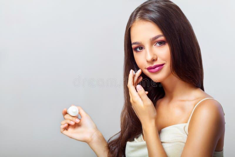 Närbild av en ung kvinna som får brunnsortbehandling isolerad white för cosmetic kräm fotografering för bildbyråer