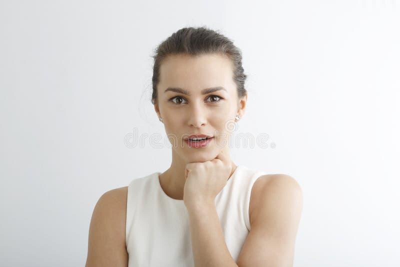 Närbild av en ung kvinna som ser upphetsad mot den vita backgrouen royaltyfria bilder