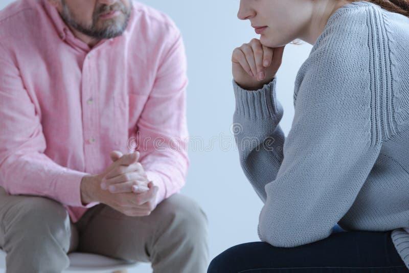 Närbild av en ung ledsen kvinna som delar hennes sorg med en psychothe arkivbilder