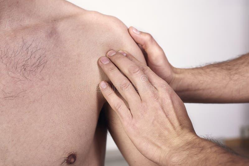 Närbild av en ung man som har chiropracticskuldrajustering r Osteopathy arkivfoton