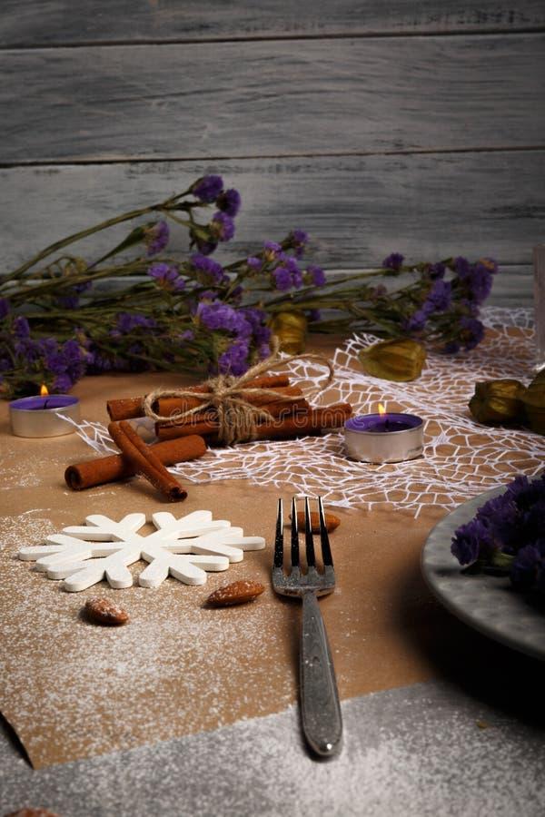 Närbild av en utsmyckad julsammansättning Lilablommor, stearinljus, kanel och en gaffel på en tabellbakgrund arkivfoton