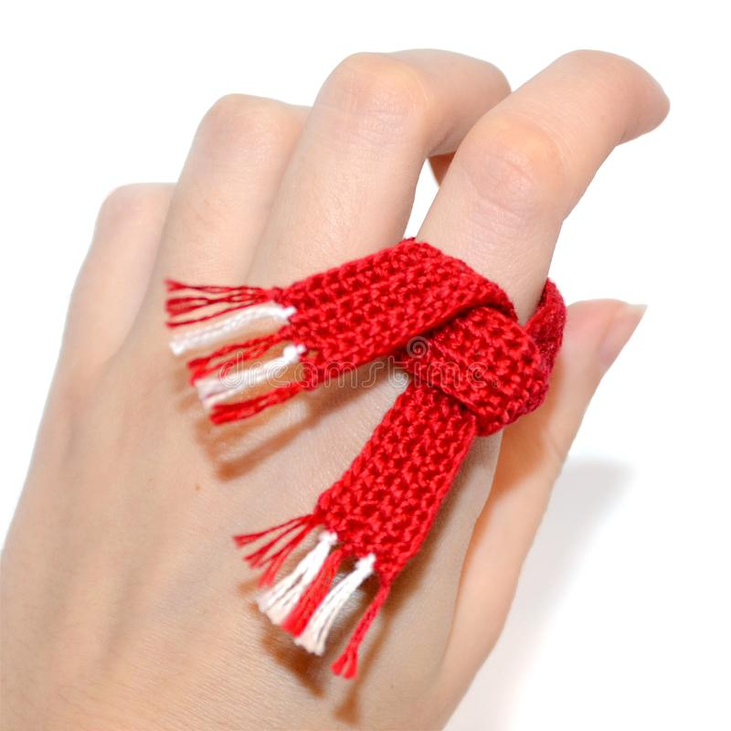 Närbild av en virkad röd och vit halsduk på handen Litet s arkivbilder