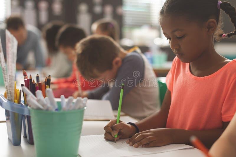 Närbild av enlopp skolaflicka som skriver på hans anteckningsbok i ett klassrum arkivbild