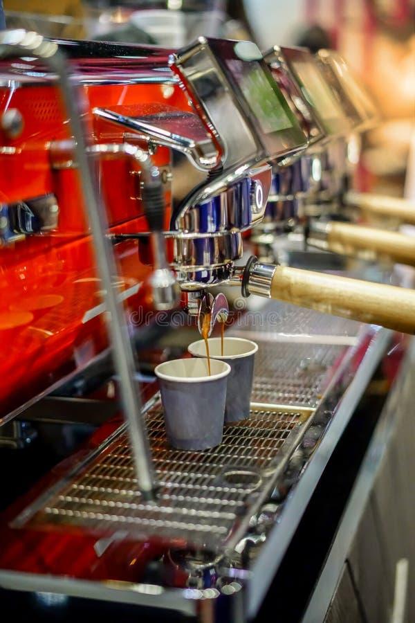 Närbild av espresso som häller från den moderna röda kaffemaskinen arkivbild