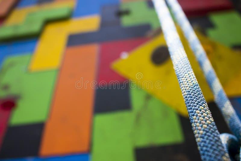 Närbild av ett blått klättringrep som framme hänger av en skämtsam idrottshallklättringvägg royaltyfria bilder