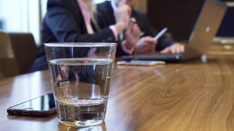 Närbild av ett exponeringsglas av vatten och en iPhone som ligger på en tabell royaltyfria bilder
