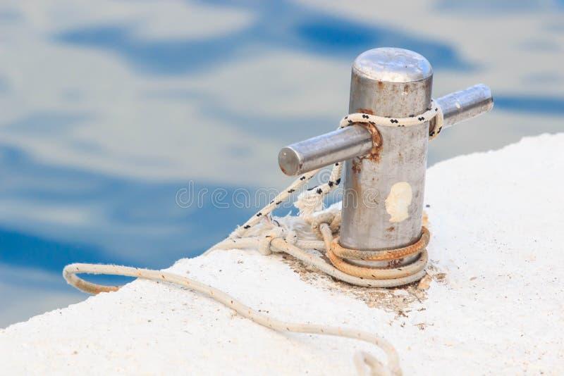 Närbild av ett förtöja rep med ett knutit slut som binds runt om en dubb på en träpir arkivfoto