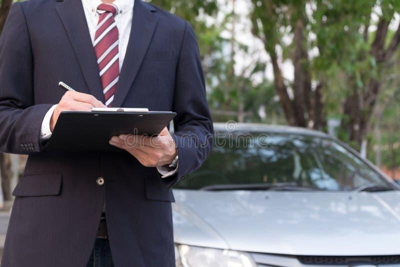 Närbild av ett mananseende i Front Of Car Holding Clipboard in royaltyfria bilder