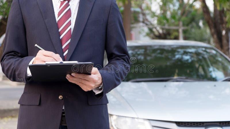 Närbild av ett mananseende i Front Of Car Holding Clipboard in royaltyfri foto