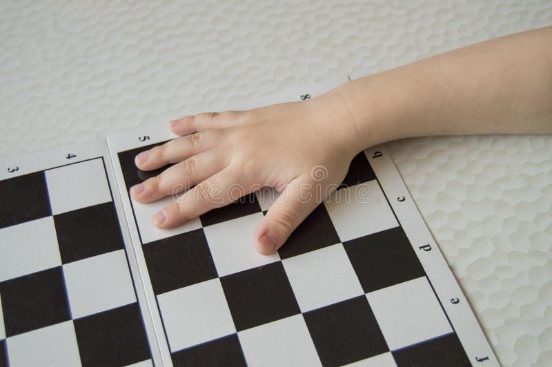 Närbild av ett småbarns hand som ligger på schackbrädet, begreppet av att lära och intellektuell utveckling av barn fotografering för bildbyråer