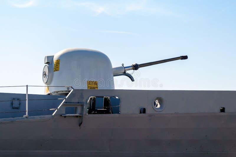 Närbild av ett torn med ett skeppvapen på en grå modern krigsskepp Skeppvapentorn med gult varnande tecken Sjö- övningar, fotografering för bildbyråer