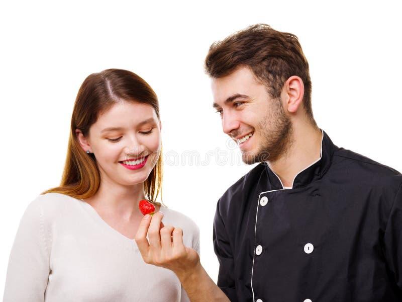 Närbild av ett ungt par, en man som matar en flicka en aptitretande jordgubbe som isoleras på en vit bakgrund arkivfoto
